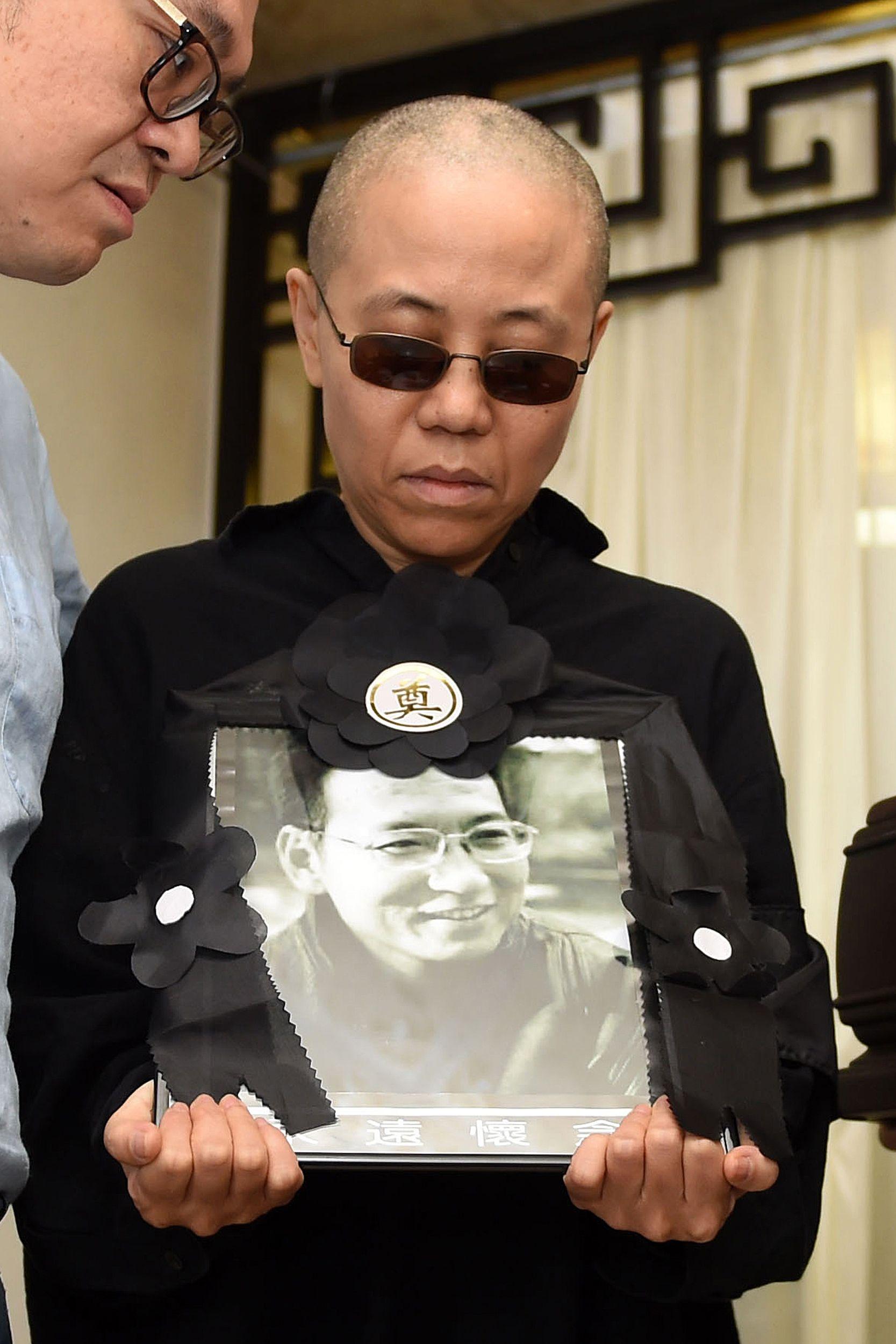 2017年7月15日劉曉波在瀋陽舉行喪禮,劉霞捧著丈夫的照片和骨灰。(Getty Images)