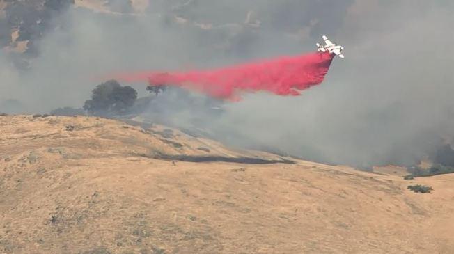 南聖荷西聖他特瑞莎公園(Santa Teresa Park)附近野地10日下午發生山火。圖為飛機在火場上空灑下滅水劑。(電視新聞截圖)