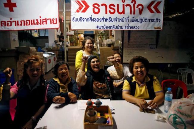 圖為志工們在聽到救援行動成功後開心慶祝的畫面。路透