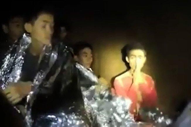 14歲的佤族少年阿杜(右)在此次泰國洞穴救援行動中,以流利的英語及禮貌的態度,擔任受困者翻譯,與英國潛水人員溝通對話。法新社