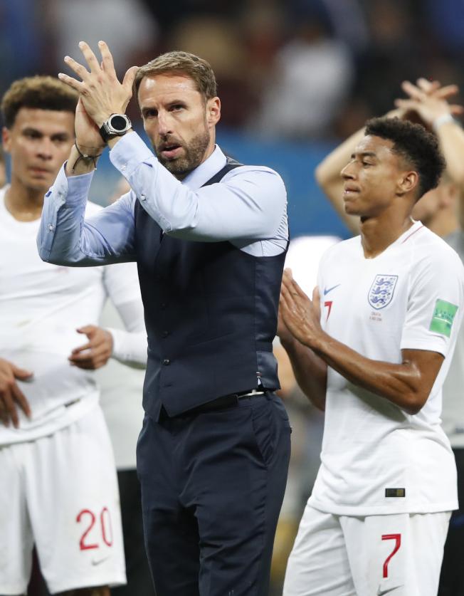 英軍爭冠夢碎,邵斯蓋特(圖中,Gareth Southgate)賽後走在球場草地上,臉色凝重,但觀眾席上不斷傳來球迷的歌聲,力挺到底。身穿招牌西裝背心的他,也對著看台上的同胞鼓掌致意。美聯社'