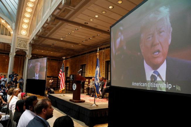 圖為在紐約曼哈頓紐約公共圖書館舉行的美國公民及移民服務局(USCIS)入籍儀式上,播放川普總統講話影片。(路透)