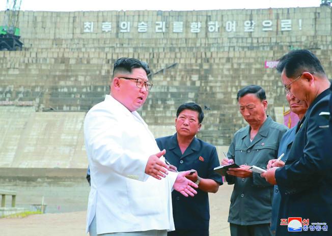 北韓官方17日發布照片,顯示金正恩(左)近日視察咸鏡北道水力發電廠的水壩工程時,因為工程進度延宕而斥責官員。(美聯社)
