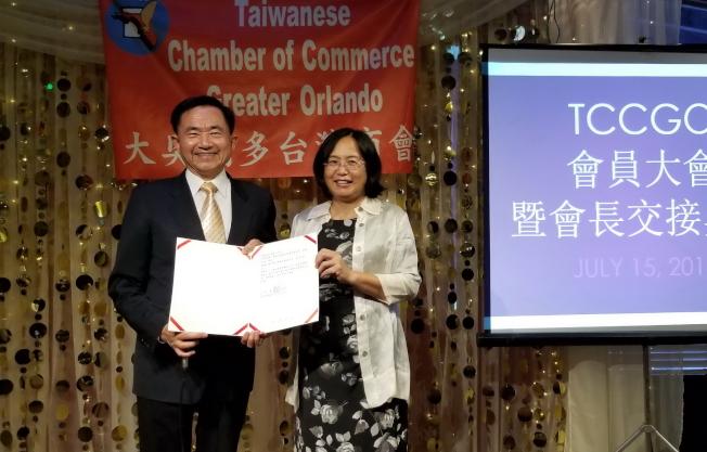 僑務委員王成章(左)代表委員長吳新興頒發獎狀給新任會長徐國鈴(右)。(記者陳文迪/攝影)