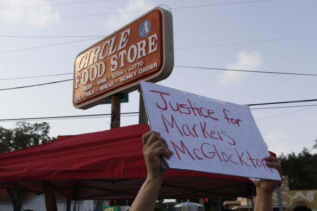 當地居民24日在Circle A便利店示威,要求還被打死的麥克拉頓一個公道。(美聯社)