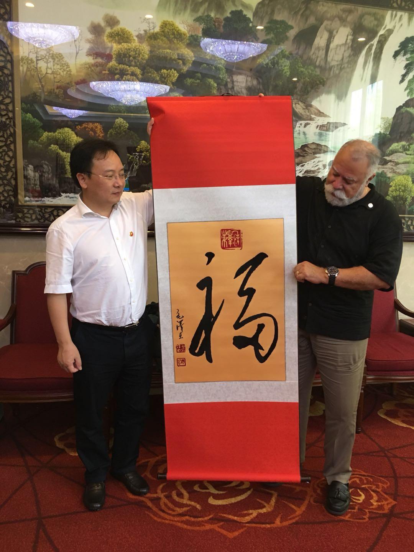 湘潭市委書記曹炯芳(左)向約巴林達市長Gene Hernandez贈送書畫禮品。(陳燦培提供)