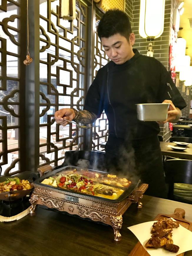 陳磊學藝三個月,讓「江邊城外」的烤魚還原正宗的萬州味兒。(記者劉大琪/攝影)