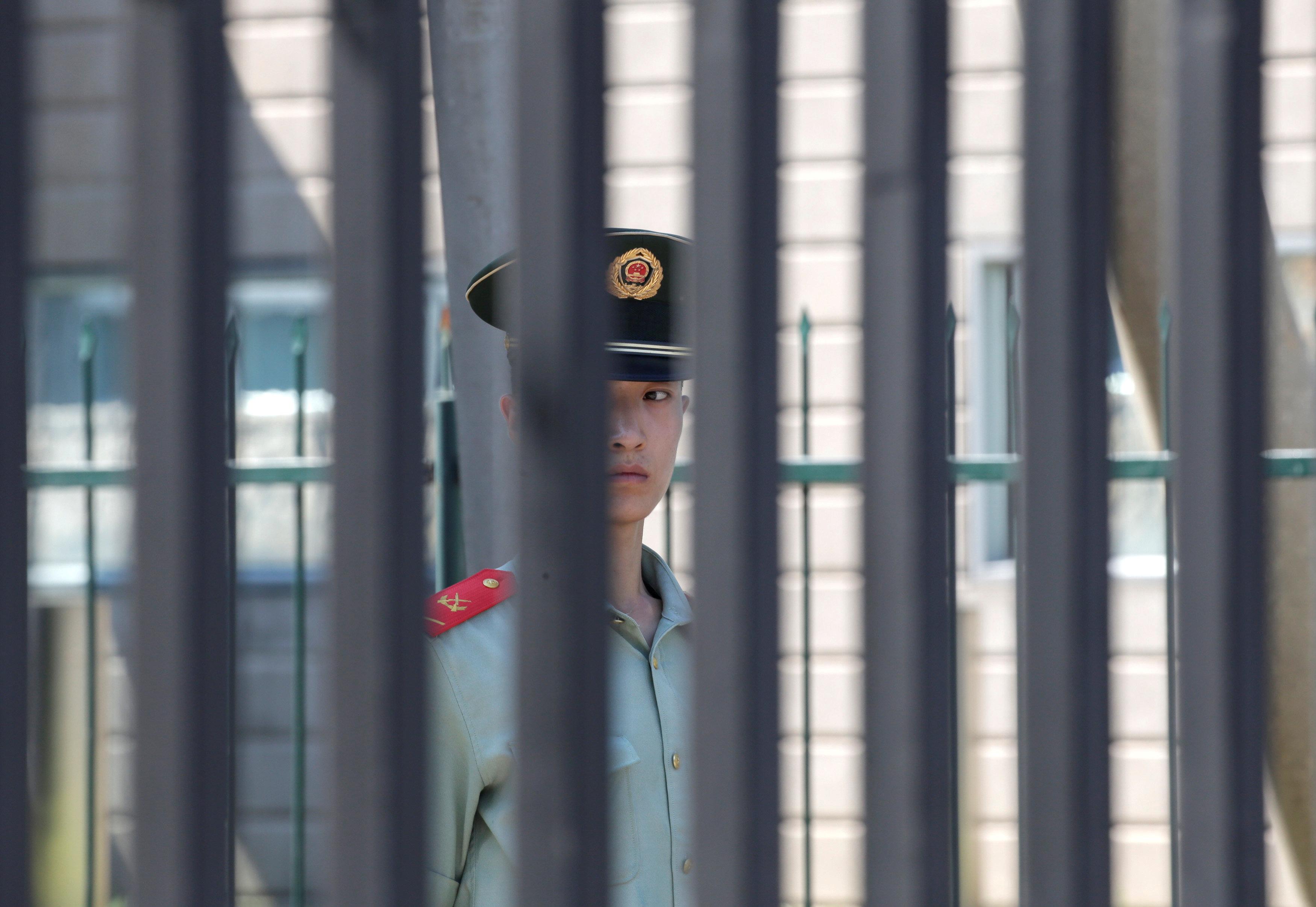 美駐北京使館傳出爆炸案後,一名武警在柵欄內守衛。(路透)