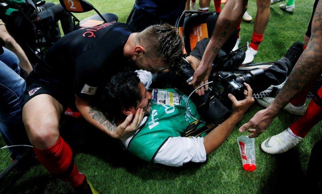 克羅埃西亞球員HIGH過頭,場邊攝影記者遭波及被壓倒在地,球員紛紛伸手將他拉起,向他道歉。 路透