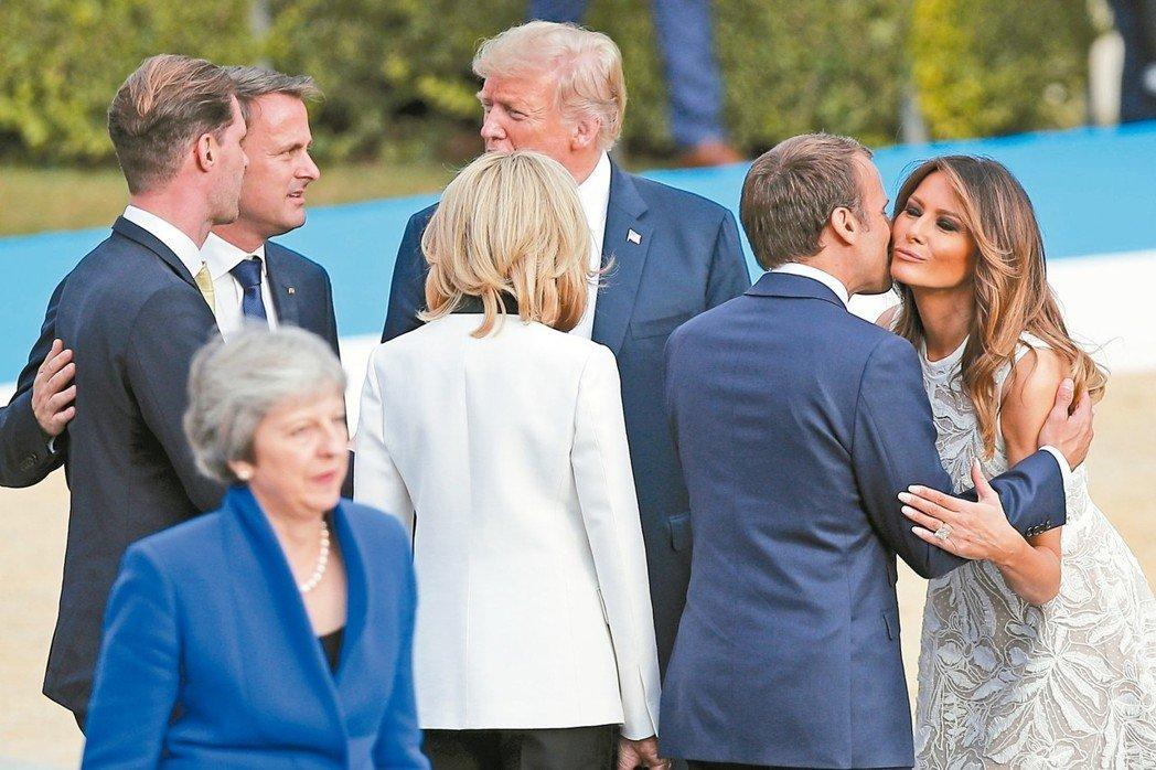 北約峰會11日拍大合照,總統川普(中)的妻子梅蘭妮亞(右一)與法國總統馬克宏(右二)打招呼。 (美聯社)
