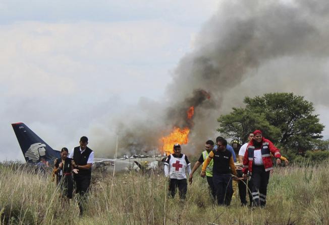 墨西哥紅十字會人員從飛機殘骸的烈焰中搶救生還者。(美聯社)