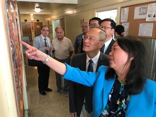 中華會館主席黃于紋(右前)向吳新興(右二)介紹會館活動照片。(特派員黃惠玲/攝影)