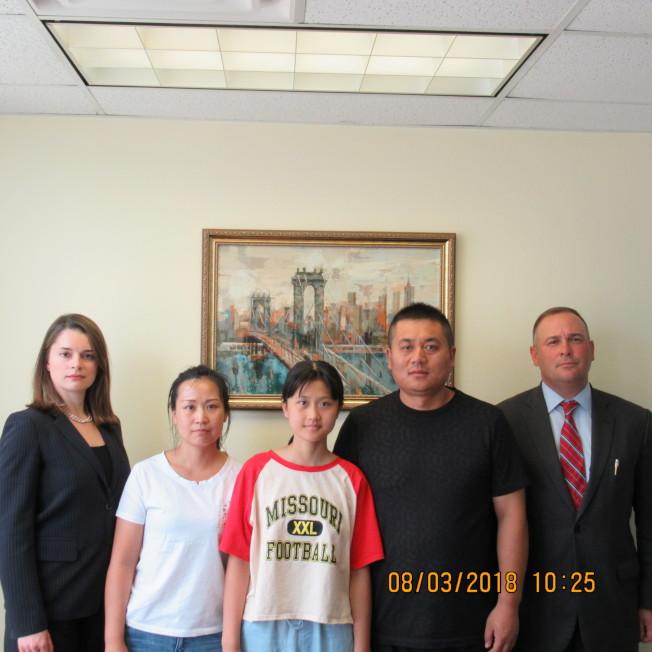 馬金晶(左三)在父母的陪同下3日現身法拉盛律師樓。左一為安娜黛蜜琪,右一為律師Mike Vista。(安娜律師樓提供)