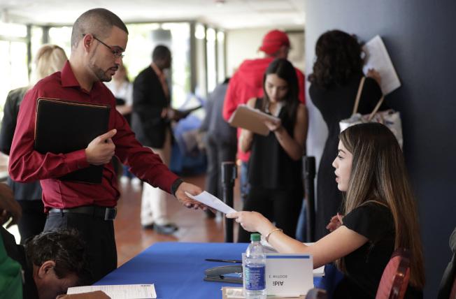 佛州求職者今年1月於邁阿密湖舉行的就業博覽會上遞交求職申請。(美聯社)