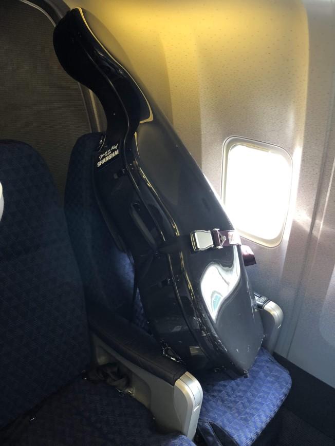 胡晶晶3日搭乘的美航班機,依照空姐要求將大提琴直接綁在座位上。(唐杰提供)