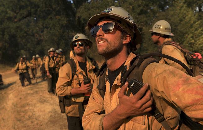 在靠近卡爾大火附近的救火員目視飛來支援的直升機。(美聯社)