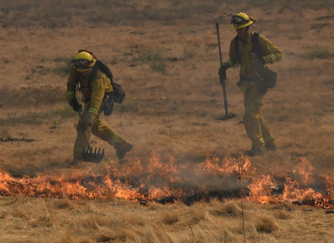 救火員正在撲滅突然冒出的火苗。(美聯社)