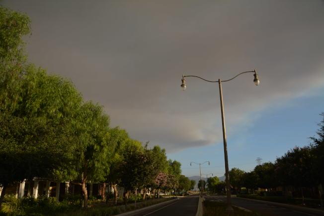 科洛纳市6日午后野火烧至超过千亩,野火浓烟在临近城市奇诺市上空。(记者启铬/摄影)