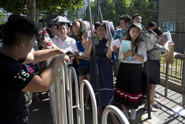 傳出美國設限嚴審中國人來美簽證,特別是科技類人才。上圖為上月在北京美國駐中國大使館前熱暑下,申請者大排長龍等候簽證面談。(美聯社)