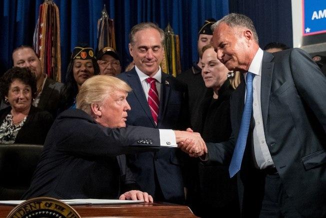 2017年4月27日川普總統簽署關於退伍軍人問題的行政命令。圖為川普總統(左)與漫威娛樂集團主席波爾莫特爾(右)握手。中為前退伍軍人事務部長舒肯。(美聯社)