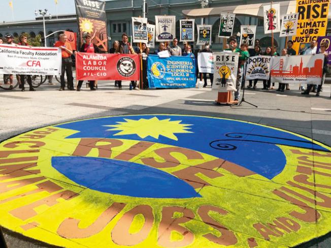 環保及勞工團體8日在舊金山港務大樓前舉行集會,並在廣場即席繪畫一幅地面壁畫,呼籲各界於一個月後的9月8日,齊來參加名為「為氣候變化、就業及正義站起來」的遊行集會,向各界宣示愛惜地球環境的重要。 參與策畫下月遊行集會的「亞太裔環境聯絡網」代表指出,州長布朗未盡支持環保工作,以近日仍在擴大的北灣大火為例,砍掉更多樹林並不能避免山火的發生,州府應該謀求更保持環境生態的途徑改善山火問題。(圖與文:記者李秀蘭)