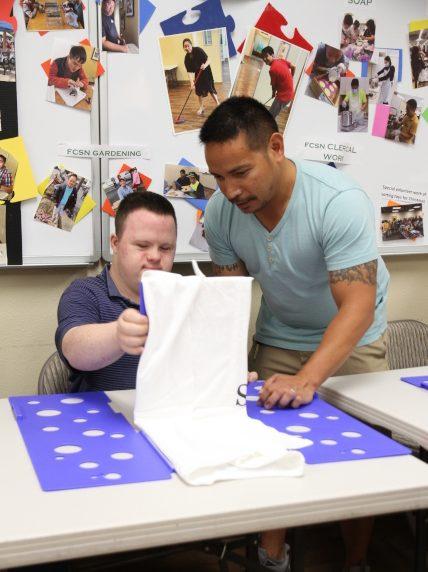 華人特殊兒童之友會訓練學員摺衣服,並輔助尋找就業機會。(記者李榮/攝影)