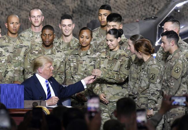 川普渡假12天後返回華府,途中在紐約州壯堡(Fort Drum)陸軍基地簽署國防授權法案(NDAA)。(美聯社)