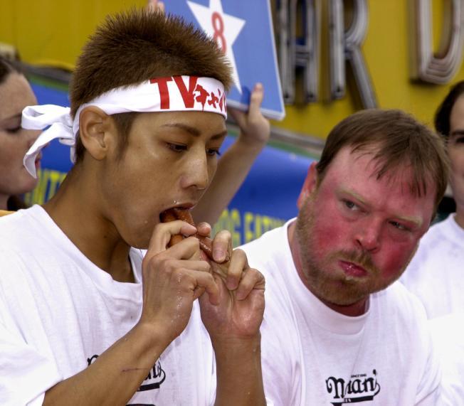 小林尊(左)在2001年初次參加「納森國際吃熱狗大賽」,旁邊的參賽者看著他,露出不可置信的表情。(Getty Images)