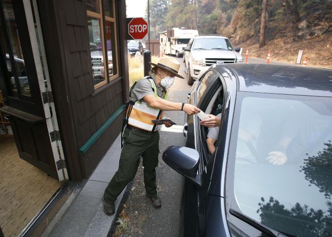 優勝美地國家公園入口園警都戴口罩。(美聯社)