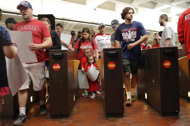 球迷穿著支持球隊的隊服走出地鐵站,準備參加華府冰球隊贏得史丹利杯勝利遊行。(美聯社)