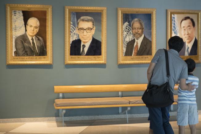聯合國前秘書長安南逝世,圖為一對日本父子遊客當天在紐約聯合國總部安南畫像前駐足。(美聯社)