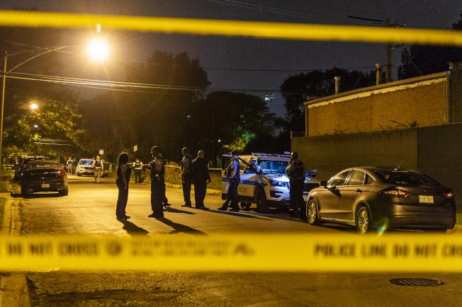 芝加哥過去這個周末再次成為「戰區」。三天內至少61人遭槍擊、其中8人喪生;平均每小時就有一人中彈。圖為警方調查一處槍擊案現場。(美聯社)