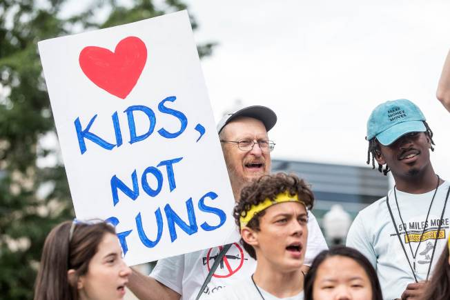 示威者在麻州史密斯威森槍枝工廠前舉牌,要求「愛孩子,而非愛槍」。(Getty Images)