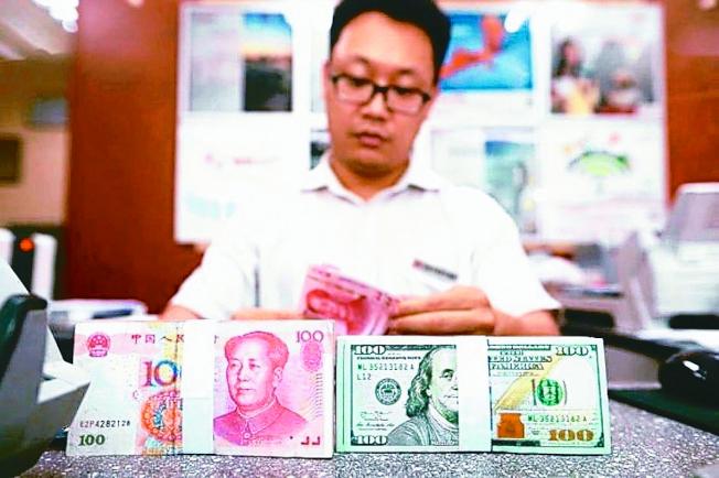 圖為銀行行員在清點鈔票。 (本報資料照片)