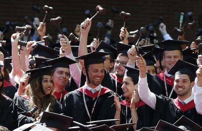 哈佛大學法學院畢業生手持法槌慶祝畢業。(美聯社)