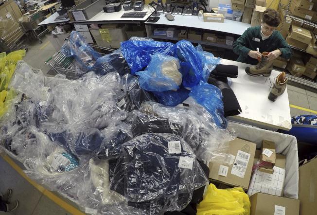 一名賣場員工在消費者退回的靴子做記號,許多退貨商品堆積在一旁。(美聯社)
