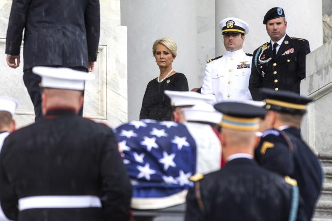 馬侃遺孀辛蒂(左起)及兒子傑克、吉米注視馬侃的靈柩抬進國會。(歐新社)