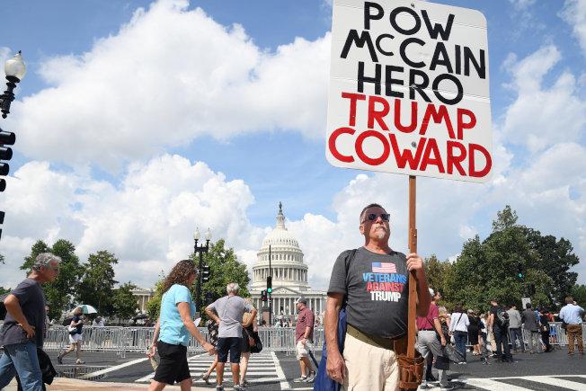國會外等候瞻仰馬侃靈柩的民眾大排長龍,有人手持標語稱「戰俘馬侃英雄,川普懦夫」。(路透)