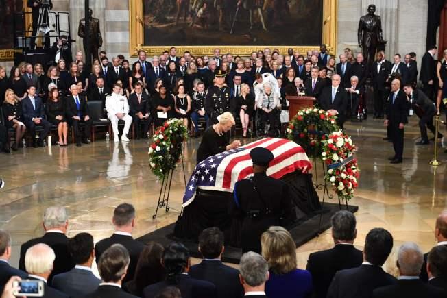 马侃的妻子伫立棺木前,后方为马侃家人。(Getty Images)