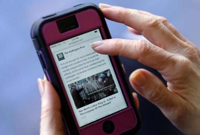 在數位化時代,民眾逐漸習慣用電腦或智慧手機閱讀文章。(美聯社)