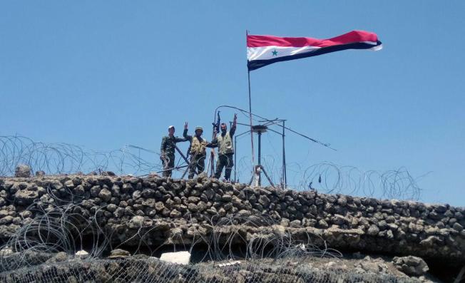 敘利亞政府軍準備進攻反抗軍在伊德利布省的最後據點。圖為政府軍7月奪回塔勒哈拉後,升國旗慶祝。(美聯社)