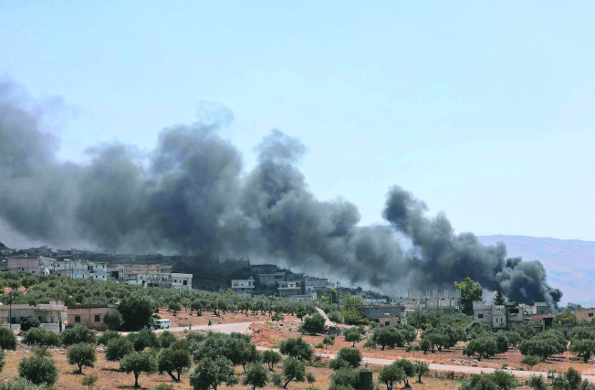 敘利亞伊德利布省4日遭俄國空襲,起火的建築物冒出濃煙。(Getty Images)