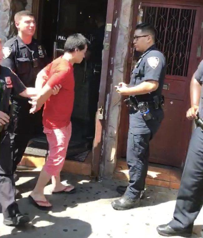 鬧場的紅衣男子被警方逮捕帶出。(視頻截圖,讀者提供)