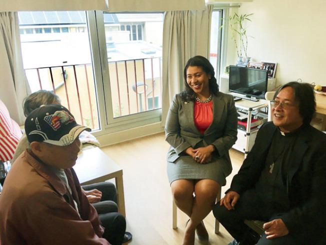 市長布里德(中)在華協中心行政主任方小龍牧師(右)陪同下到訪居民楊勝(左)所居住的單位。(圖片由舊金山市長新聞辦公室提供)