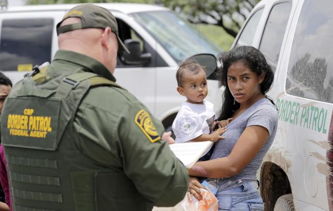 移民及海關執法局(ICE)和邊境巡邏人員在2017年遇襲的次數,達到2010年以來的高峰,顯示非法移民日漸想與執法人員抗爭而不是逃避。圖為抱著小孩的非法移民向邊境巡邏員自首。(美聯社)