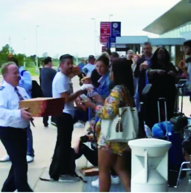 美國航空公司機長為了不讓乘客挨餓,親自將披薩送到乘客手上。取材自CNN