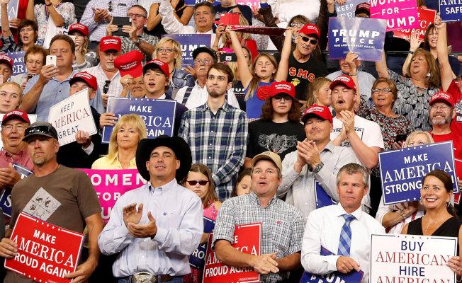 川普總統在蒙大拿州造勢,全場狂熱支持川普,獨有圖中這名穿格子襯衫青年抱著雙手,露出不同意川普說法的神情,與周遭群眾格格不入。(路透)