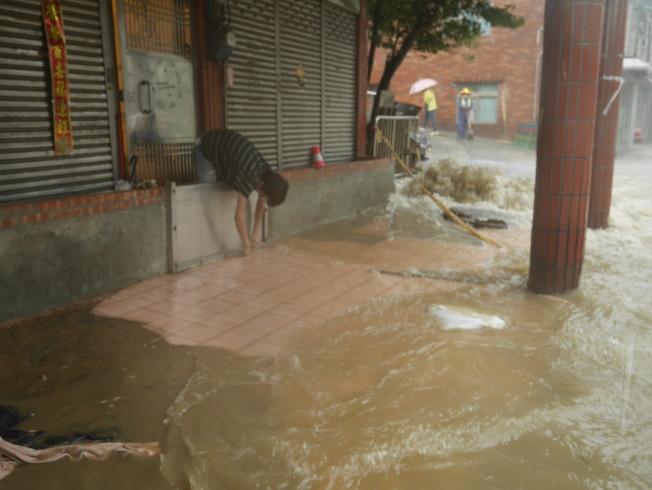 在7-11德復門市上班的黃得倫,跑去水災受災戶謝姓婦人家,幫忙關上攔水鐵門,清掃淹水。記者吳淑君/攝影