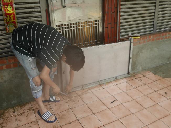 在7-11德復門市上班的黃得倫,跑去這次淹水首當其衝的謝姓婦人家,幫忙關上攔水鐵門,清掃淹水。 記者吳淑君/攝影