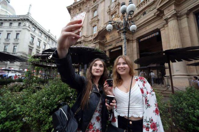 外國遊客也在星巴克新開的米蘭店外自拍留影紀念。歐新社